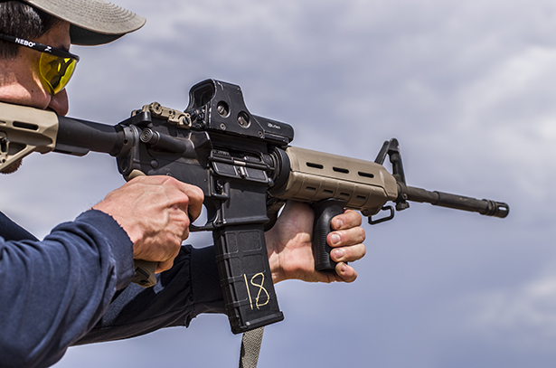 A man firing a Bushmaster AR-15.